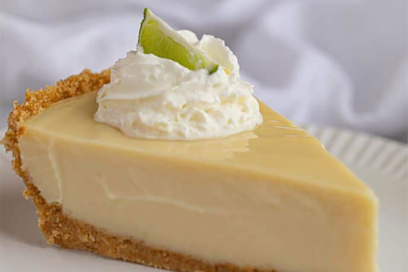 Slice of key lime pie topped with whipped cream and lime on white plate