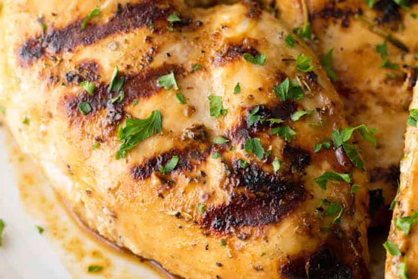 Grilled chicken topped with herbs on white plate