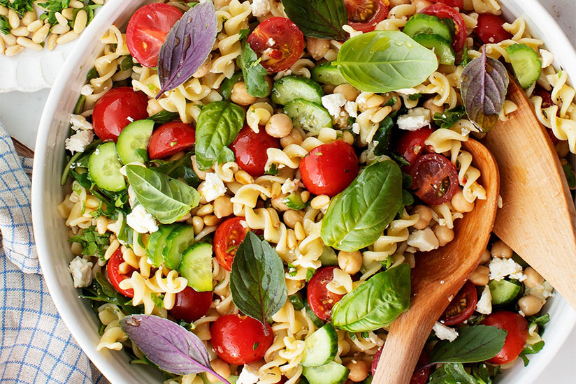 Mediterranean pasta salad in white bowl with salad servers on counter