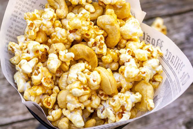 Caramel popcorn with cashews wrapped in newspaper