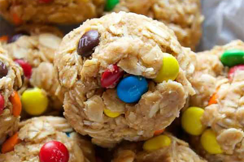 No-bake energy balls with oats and M&Ms inside dish lined with wax paper