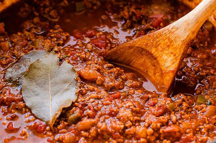Texas no beans chili with bay leaf and wooden spoon