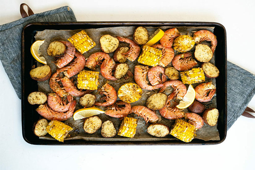 Oven-cooked shrimp with corn and potatoes on baking tray on counter