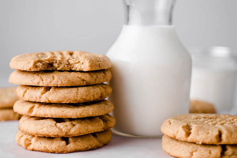Peanut butter cookies stacked beside glass pitcher of milk