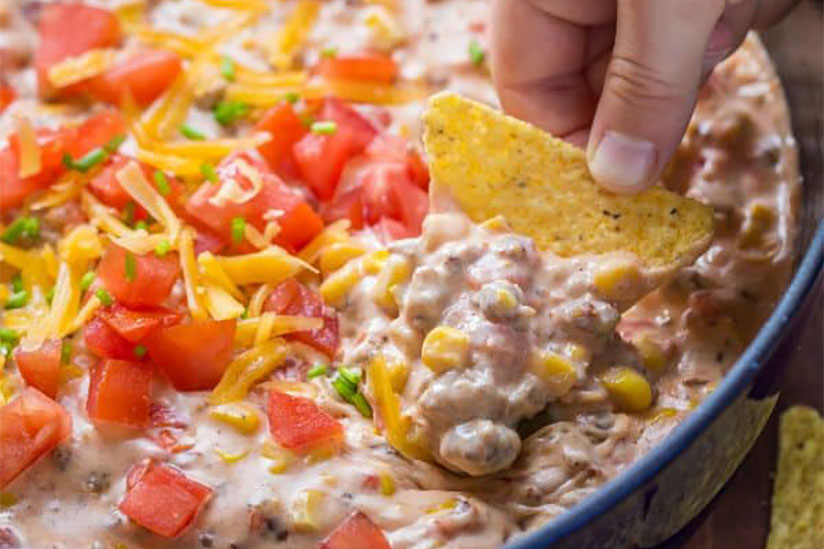 Hand with tortilla chip dipping into sausage queso in blue dish