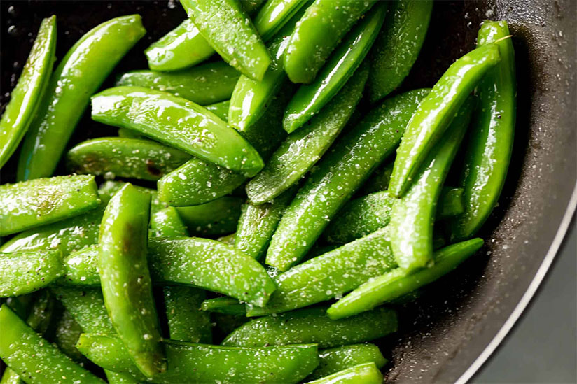 Sauteed snap peas cooking in pan on dark background