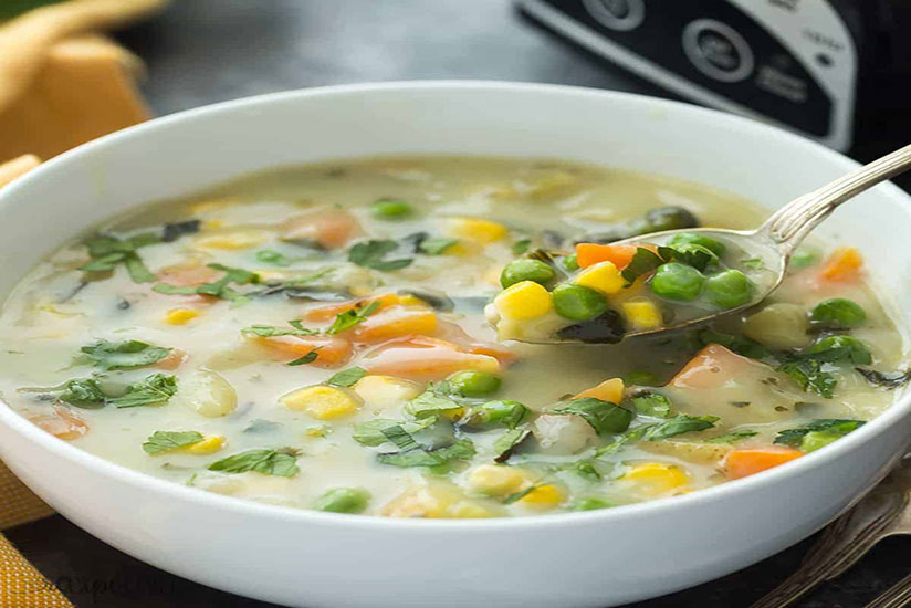 Spoon scooping creamy vegetable soup with green peas, corn, and carrots in bowl
