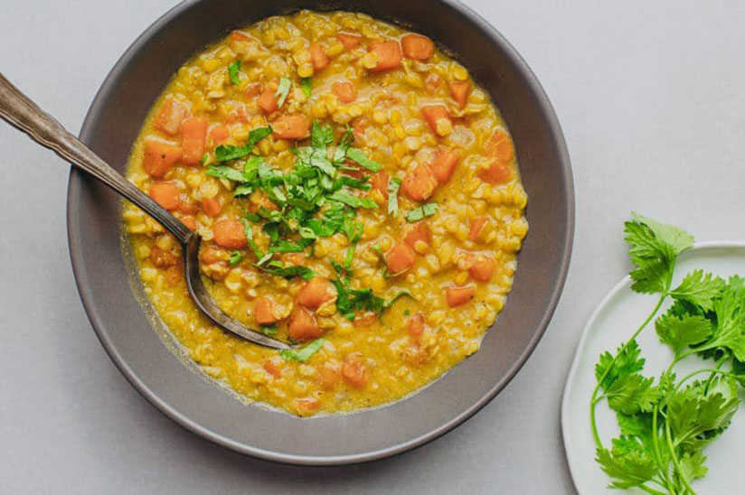 Slow cooked sweet potato and lentil curry with spoon in copper pan on counter