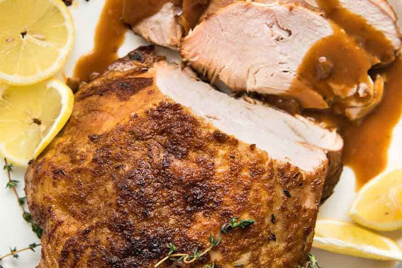 Slow cooked turkey on white plate with some slices carved and drizzled with gravy