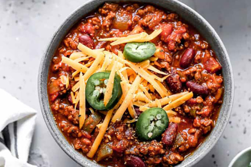 Spicy chili topped with cheese and jalapenos in a bowl on marble counter