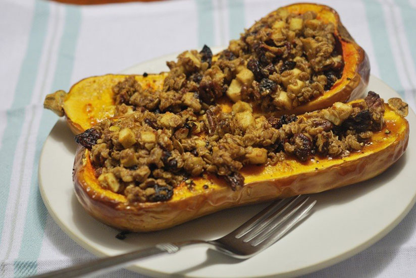 Stuffed butternut squash on white plate with fork on white tablecloth