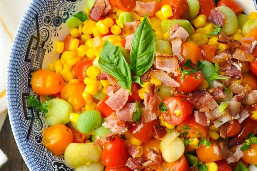 Succotash topped with diced bacon and herbs in blue bowl on counter