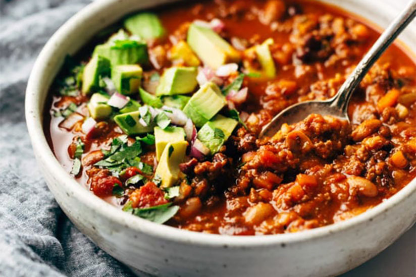 Sunday Chili topped with sliced avocados with metal spoon in white bowl