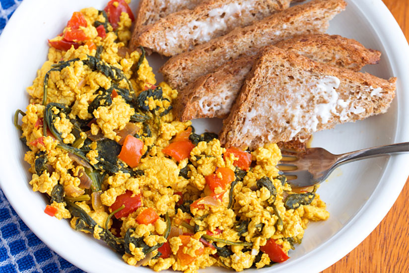 Tofu scramble with sliced tomatoes and toast on white plate