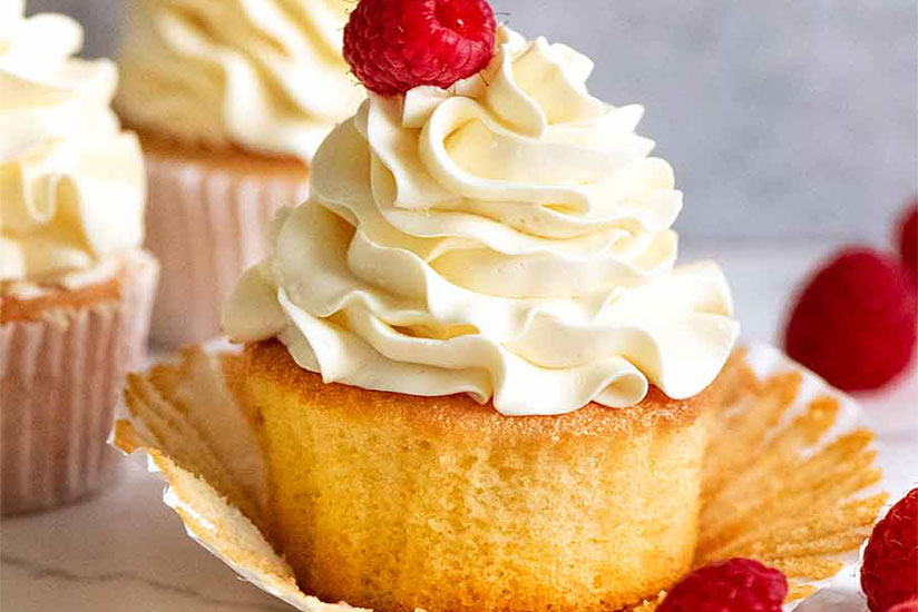 Vanilla cupcake topped with vanilla buttercream frosting and raspberry