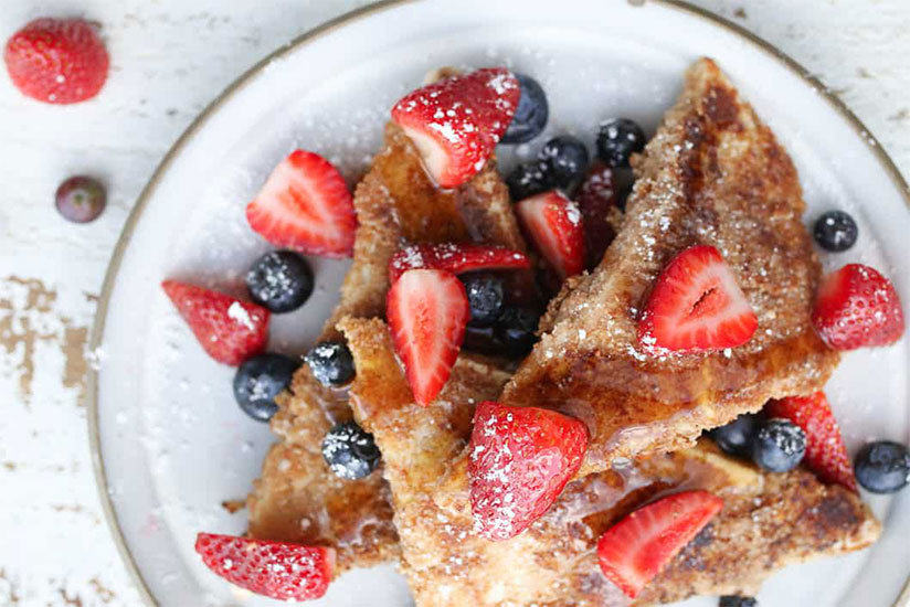 French toast tofu topped with sliced strawberries and blueberries on plate