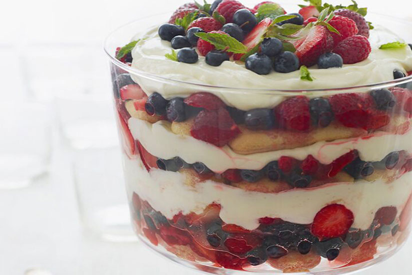 Layered Summer trifle of ladyfinger, cream, strawberries, and blueberries in glass dish
