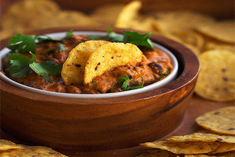 Two tortilla chips dipped in black bean chili cheese in wooden bowl