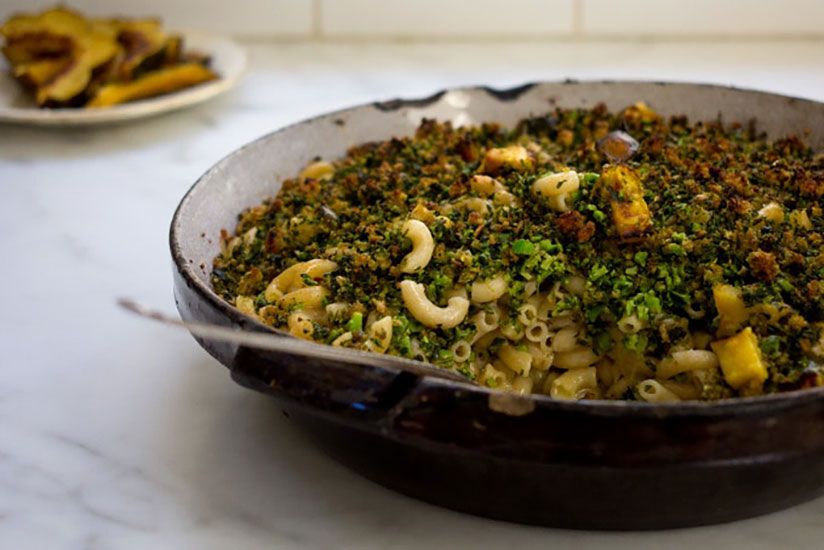 Broccoli basil mac and cheese with spoon in brown dish on counter