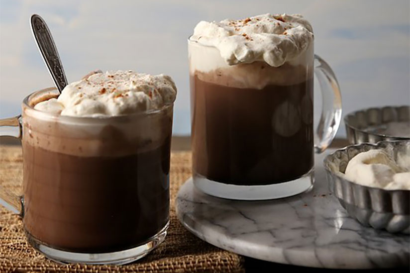 Hot chocolate in two clear mugs topped with whipped cream