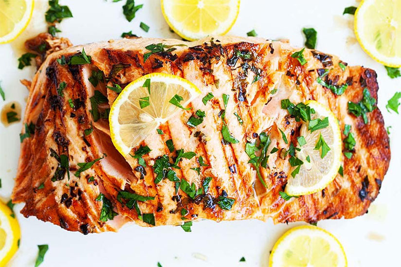 Grilled salmon topped with herbs and sliced lemons on white plate