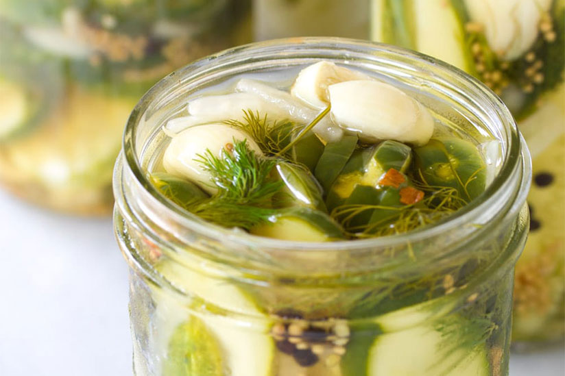Refrigerator pickles in opened jar on white counter