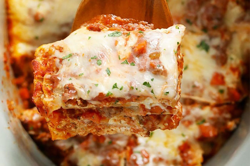 Lasagna on top of wood spoon with lasagna dish on background