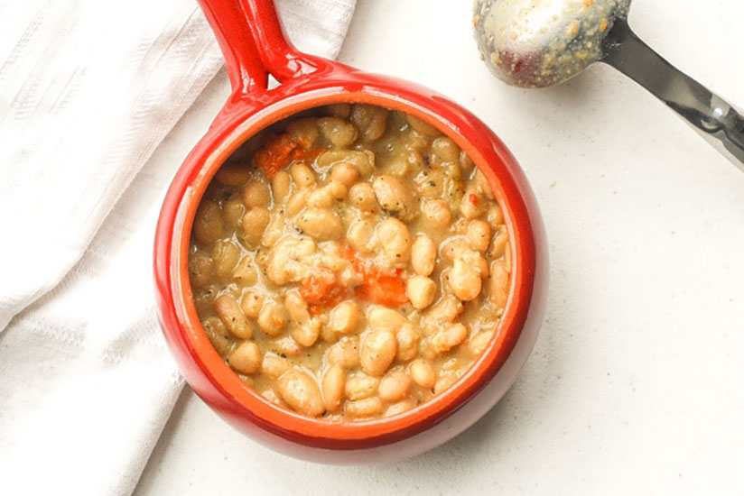 Lima beans with sprinkle of seasoning on top in red bowl on marble counter