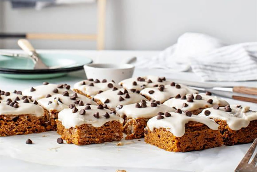Square-cut pumpkin bars topped with icing and chocolate chips on counter