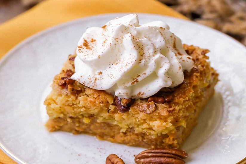 Slice of pumpkin dump cake topped with whipped cream and cinnamon powder