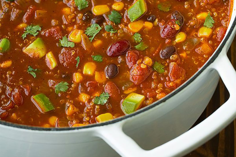 Quinoa chili with diced avocados in white pot