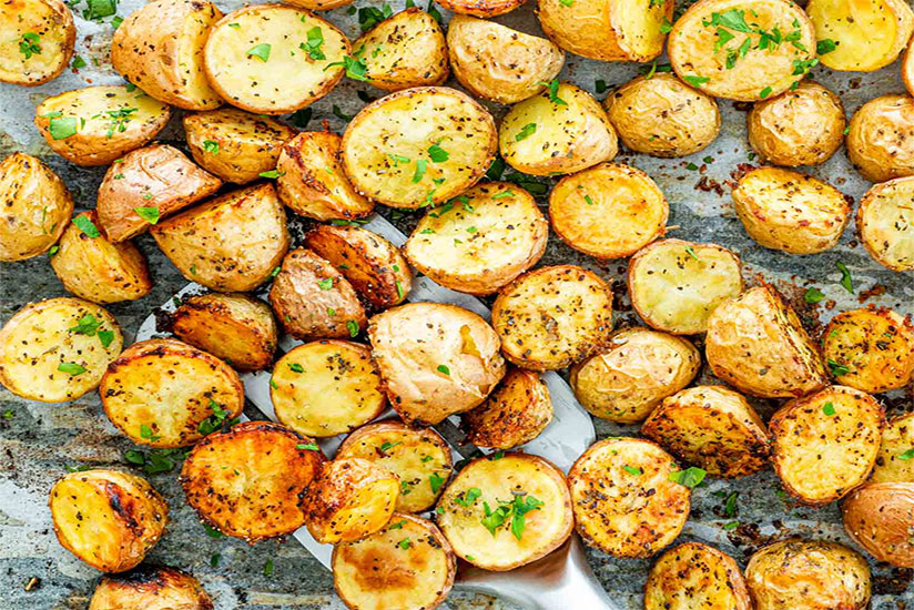 Halved roasted potatoes garnished with herbs on gray counter