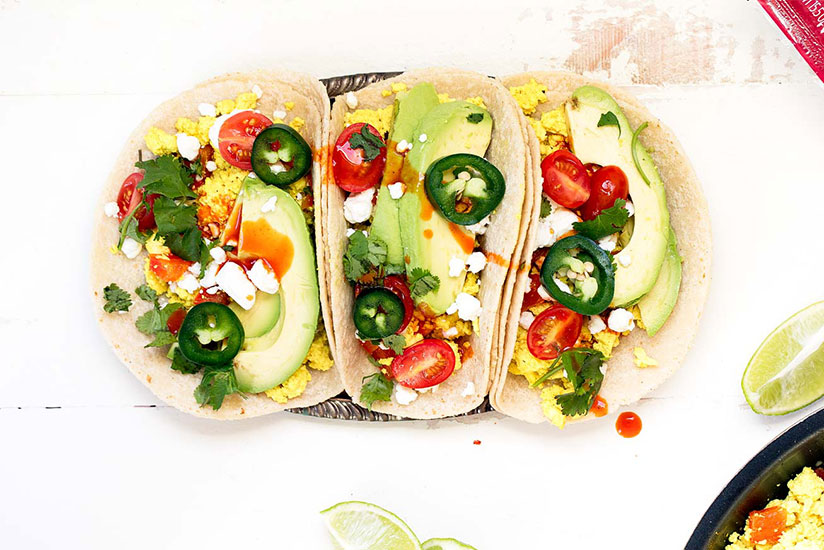 Scrambled tofu tacos topped with sliced avocados and jalapenos on counter
