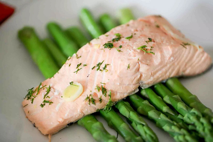 Poached salmon on top of asparagus spears on white plate