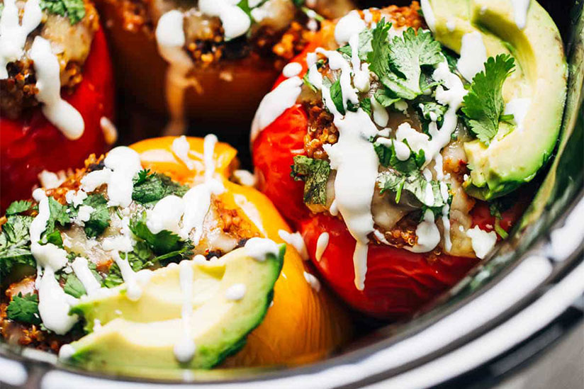 Black bean quinoa stuffed peppers topped with sliced avocados in crockpot