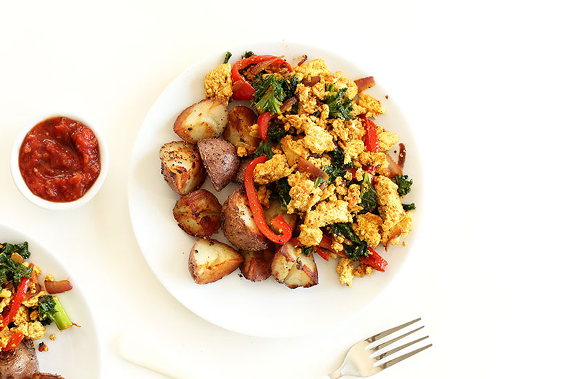 Tofu scramble with sliced potatoes on white plate on counter