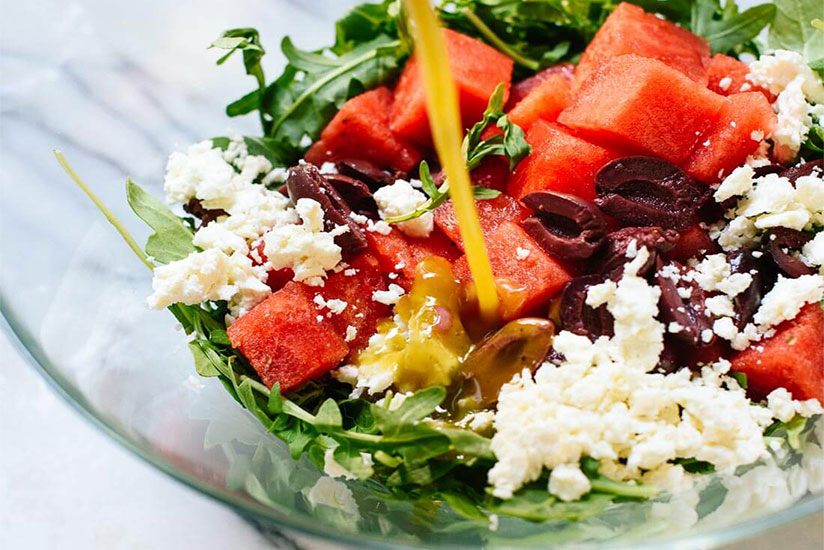Arugula watermelon salad poured with vinaigrette in clear bowl