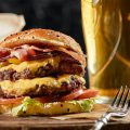 Cheese burger beside glass of beer on counter