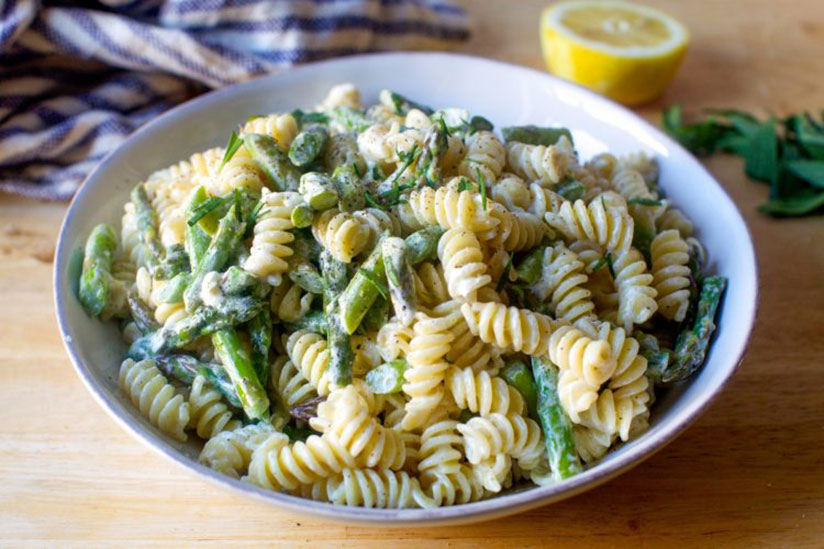 Asparagus and goat cheese pasta in white bowl on wood counter