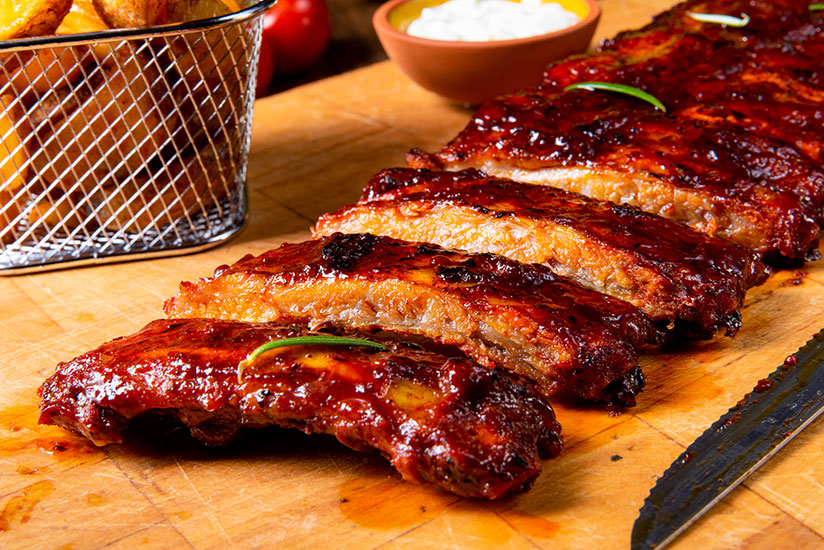 Sliced spare ribs on wooden chopping board beside knife