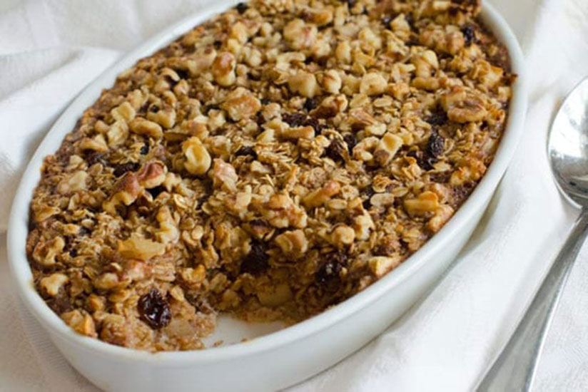 Consumed oatmeal casserole with walnuts and raisins in white dish