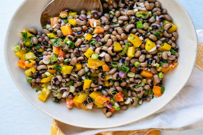 Black eyed pea salad with sliced tomatoes on white plate on counter