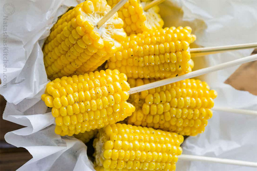 Corn on the cob on stick on top of paper