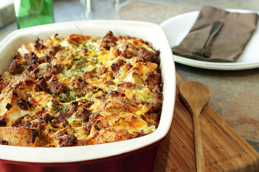 Bread pudding casserole in red and white dish on wood board