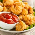 Breaded popcorn shrimp on lettuce with side of dipping sauce