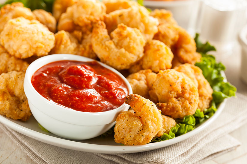 Pile of breaded shrimp on top of lettuce on white plate with cocktail sauce
