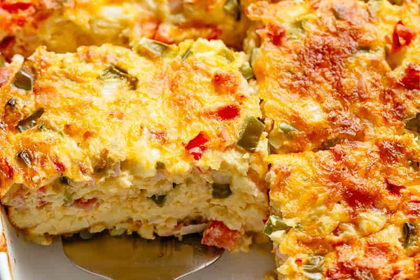 Sliced bacon and egg breakfast casserole in white dish with spatula