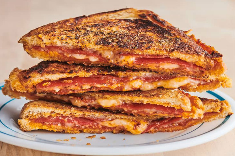 Stack of pizza sandwich on white plate with brown background
