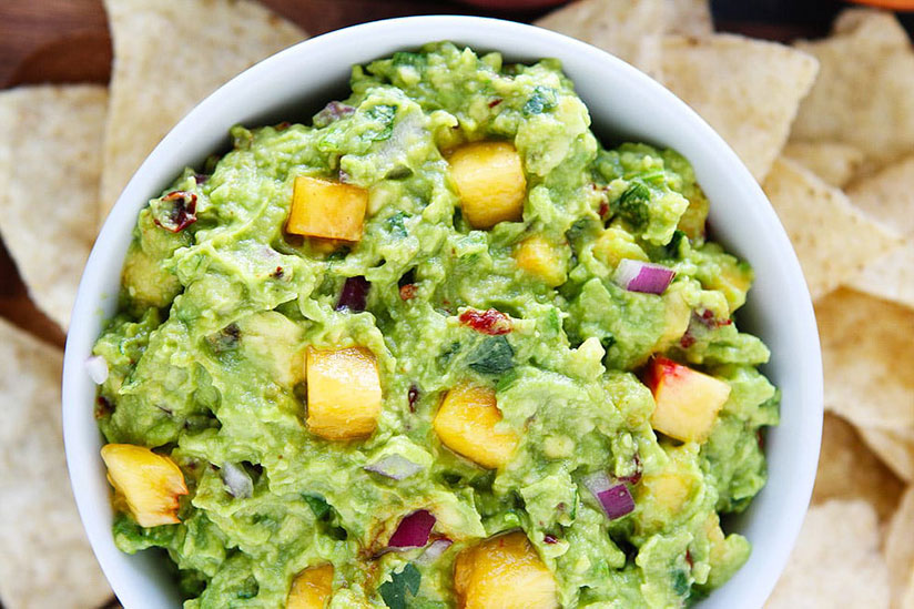 Peach guacamole sprinkled with red onions surrounded by tortilla chips