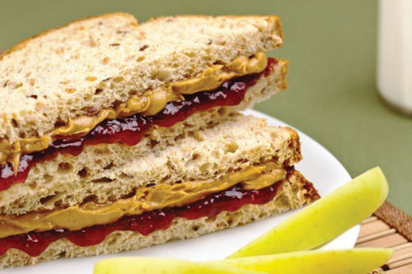 Healthy peanut butter and jelly sandwich on white plate